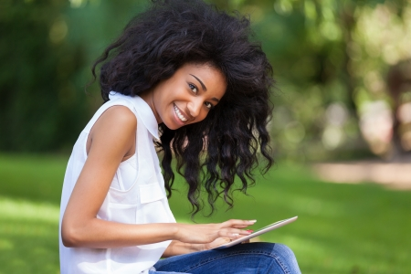 african ethnicity: Outdoor portrait of a smiling teenage black girl using a tactile tablet - African people