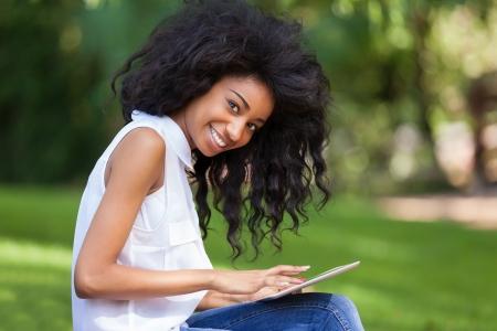negras africanas: Retrato al aire libre de una ni�a de negro adolescente sonriente con una tableta t�ctil - pueblo africano