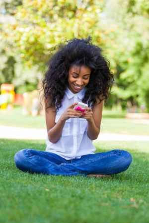 Smiling teenage black girl using a phone, sitting on the grass - African people photo