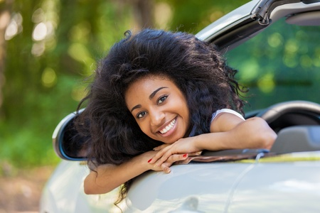 Young black teenage driver seated in her new convertible car - African people Stock Photo - 21656407