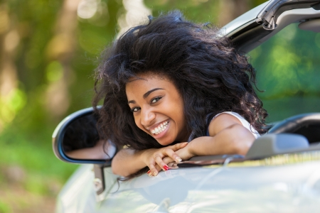 Young black teenage driver seated in her new convertible car - African people Stock Photo
