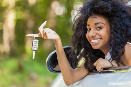 car driver: Young beautiful black teenage driver holding car keys driving her new car Stock Photo