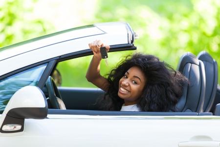 car keys: Young beautiful black teenage driver holding car keys driving her new car Stock Photo