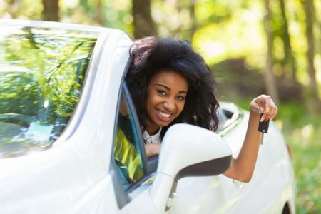 chofer: Teclas hermosas jovenes negros adolescentes Conductor titular del coche que conduce su nuevo coche Foto de archivo