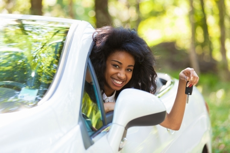 driving: Young beautiful black teenage driver holding car keys driving her new car Stock Photo