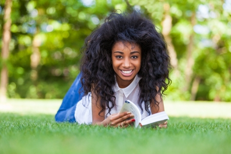 Young student girl reading a book in the school park - African people photo