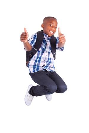 garcon africain: Afrique garçon de l'école américaine de sauter et de faire thumbs up, isolé sur fond blanc - les Noirs Banque d'images
