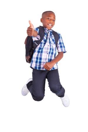 ni�os latinos: Africano ni�o de la escuela americana saltando y haciendo pulgares arriba, aislado en fondo blanco - negros