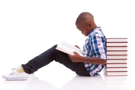 kids reading book: African American school boy reading a book, isolated on white background - Black people