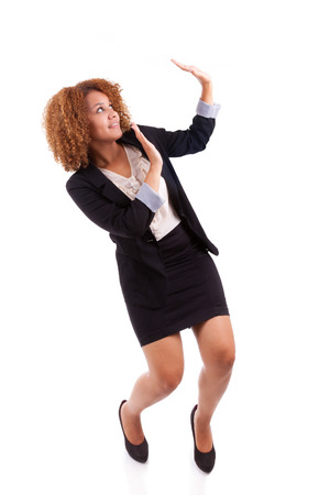 Portrait of a young african american business woman making a protection gesture, isolated - Black people photo