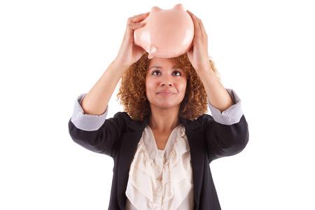 Jonge Afrikaanse Amerikaanse zakenvrouw met een spaarvarken, geïsoleerd op een witte achtergrond - Afrikaanse mensen Stockfoto