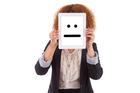 indifferent: African American business woman holding a tactile tablet displaying an indifferent emoticon, isolated on white background - Black people Stock Photo