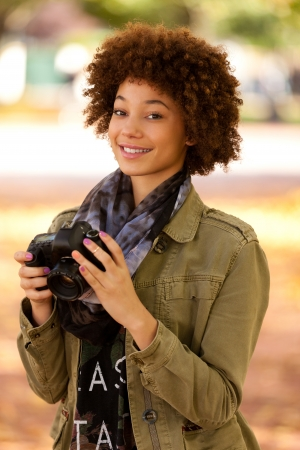 Autumn outdoor portrait of beautiful African American young woman holding a digital camera - Black people photo