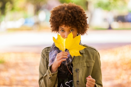 Autumn outdoor portrait of beautiful African American young woman holding yellow leaves - Black people photo