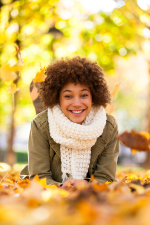 Autumn outdoor portrait of beautiful African American young woman lying down - Black people photo