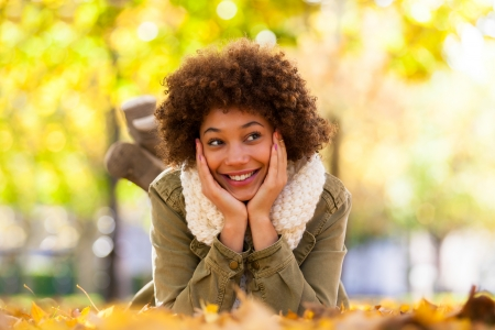 african tree: Autumn outdoor portrait of beautiful African American young woman lying down - Black people Stock Photo