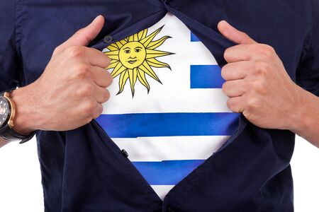 Young sport fan opening his shirt and showing the flag his country Uruguay, Uruguayan flag photo
