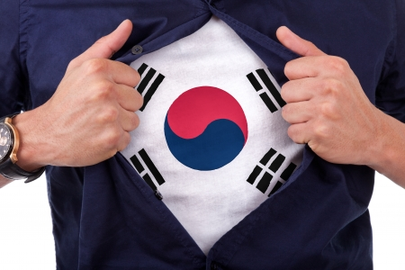 Young sport fan opening his shirt and showing the south korea flag photo