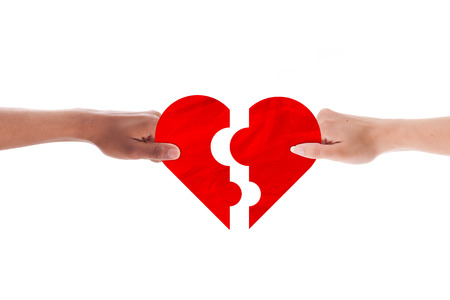 Mixed couple hands holding holding heart shape puzzle photo