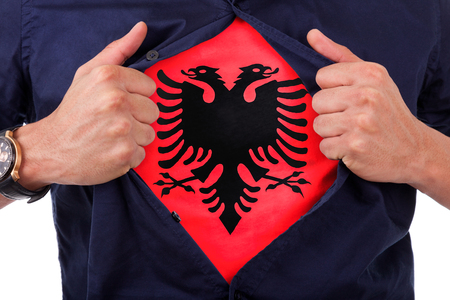 Young sport fan opening his shirt and showing the flag his country Albania, Albanian flag photo