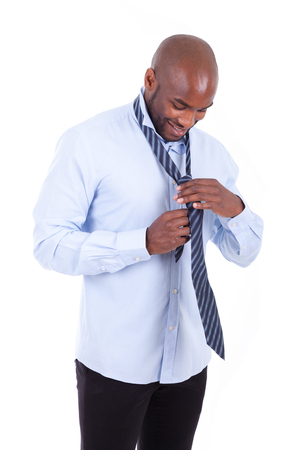 knotting: Portrait of a young African American business man knotting a tie - Black people, isolated on white background Stock Photo