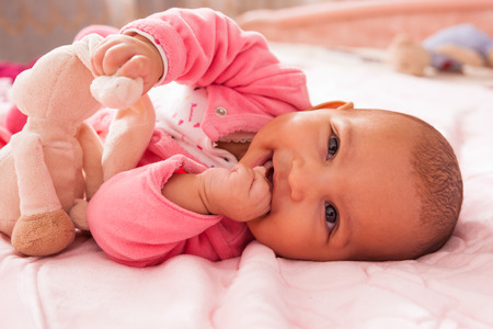 Adorable little african american baby girl playing with a plush - Black people photo