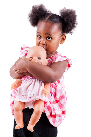 Cute little african american girl holding a doll, isolated on white background