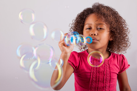 Cute little African American girl blowing soap bubbles