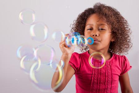 niños negros: Linda niña Afroamericana soplando pompas de jabón Foto de archivo