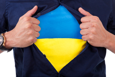 Young sport fan opening his shirt and showing the flag his country ukraine photo