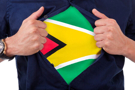 Young sport fan opening his shirt and showing the flag his country Guyana, Guyanese flag photo