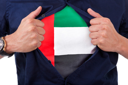 Young sport fan opening his shirt and showing the flag his country United Arab Emirates, emirati flag photo