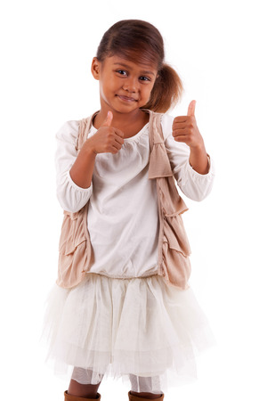 Cute little African Asian girl  making  thumbs up gesture,  over white background photo
