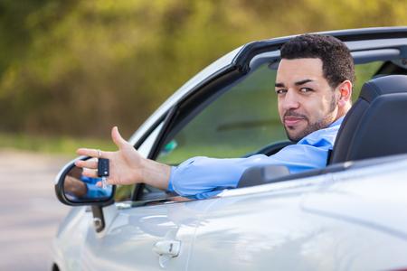 Young black latin american driver holding car keys driving his new car photo