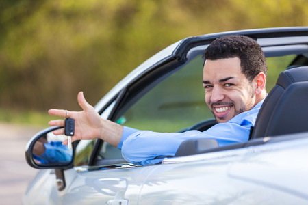 brazilian caribbean: Young black latin american driver holding car keys driving his new car