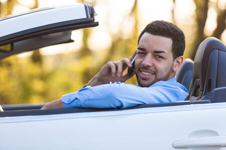 Young latin american driver making a phone call while driving photo