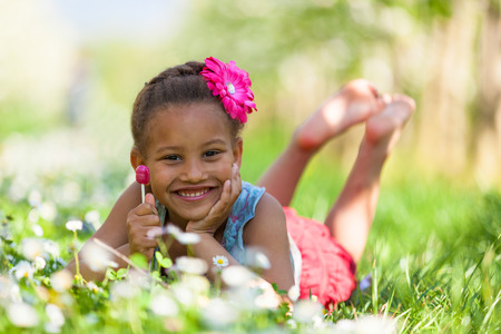 Outdoor portrait of a cute young black girl  lying down on the grass and smiling - African people Stock Photo