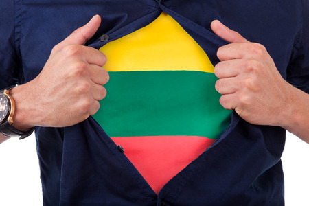 national hero: Young sport fan opening his shirt and showing the flag his country Lithuania