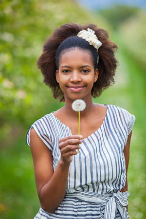 Outdoor portrait of a young beautiful african american woman holding a dandelion flower - Black people photo
