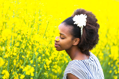 curly hair model: Outdoor portrait of a young beautiful african american woman in a rape colza field - Black people Stock Photo
