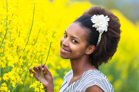 afro caribbean ethnicity: Outdoor portrait of a young beautiful african american woman in a rape colza field - Black people Stock Photo