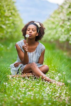 personnes noires: Outdoor portrait d'une belle jeune femme afro-am�ricaine soufflant une fleur de pissenlit - les Noirs
