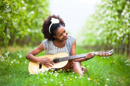personnes noires: Outdoor portrait d'une belle jeune femme am�ricaine jouant de la guitare africaine - les Noirs Banque d'images