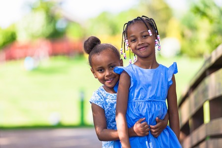 african american woman hair: Outdoor  portrait of a cute young black sisters smiling - African people - African people Stock Photo