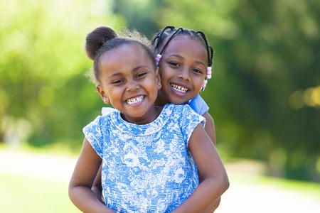 Retrato al aire libre de una linda hermanas negros jóvenes riendo - pueblo africano