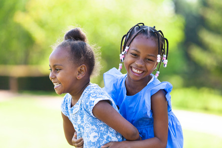 children playing outside: Outdoor  portrait of a cute young black sisters laughing - African people