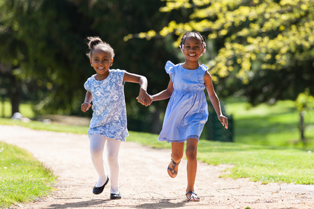 babies playing outside: Outdoor  portrait of a cute young black sisters running - African people