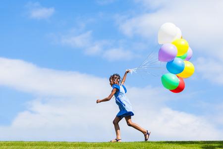 Openlucht portret van een leuk jong klein zwart meisje spelen met ballonnen - Afrikaanse mensen Stockfoto
