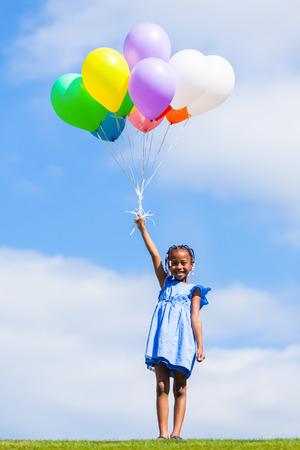 fille noire: Outdoor portrait d'une jeune petite fille noire mignonne jouant avec des ballons - Africains