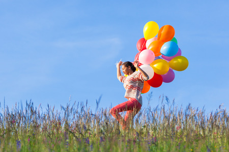 Outdoor portrait of a young African American teenage girl running with balloons photo